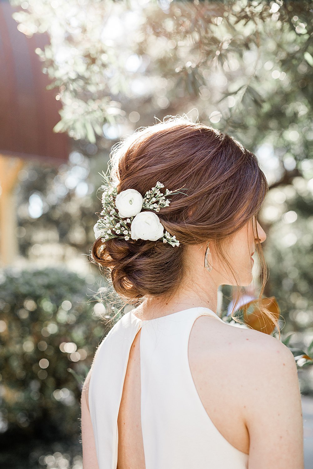 White and Green florals placed in messy bun for bride's hairdo