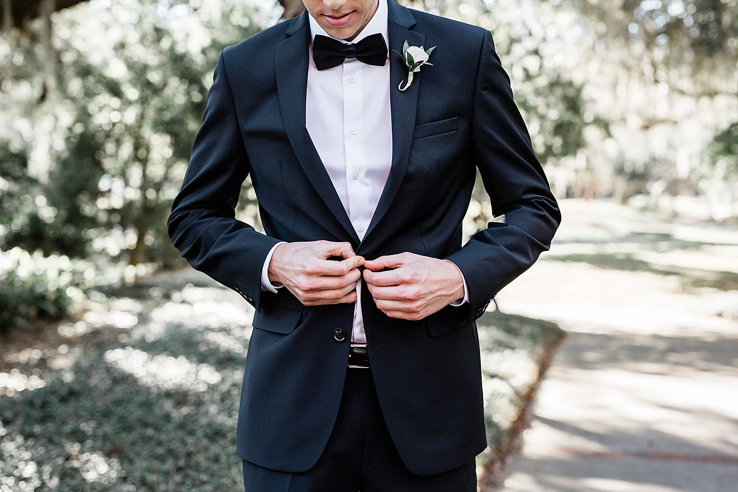 Groom buttons his jacket on his black suit