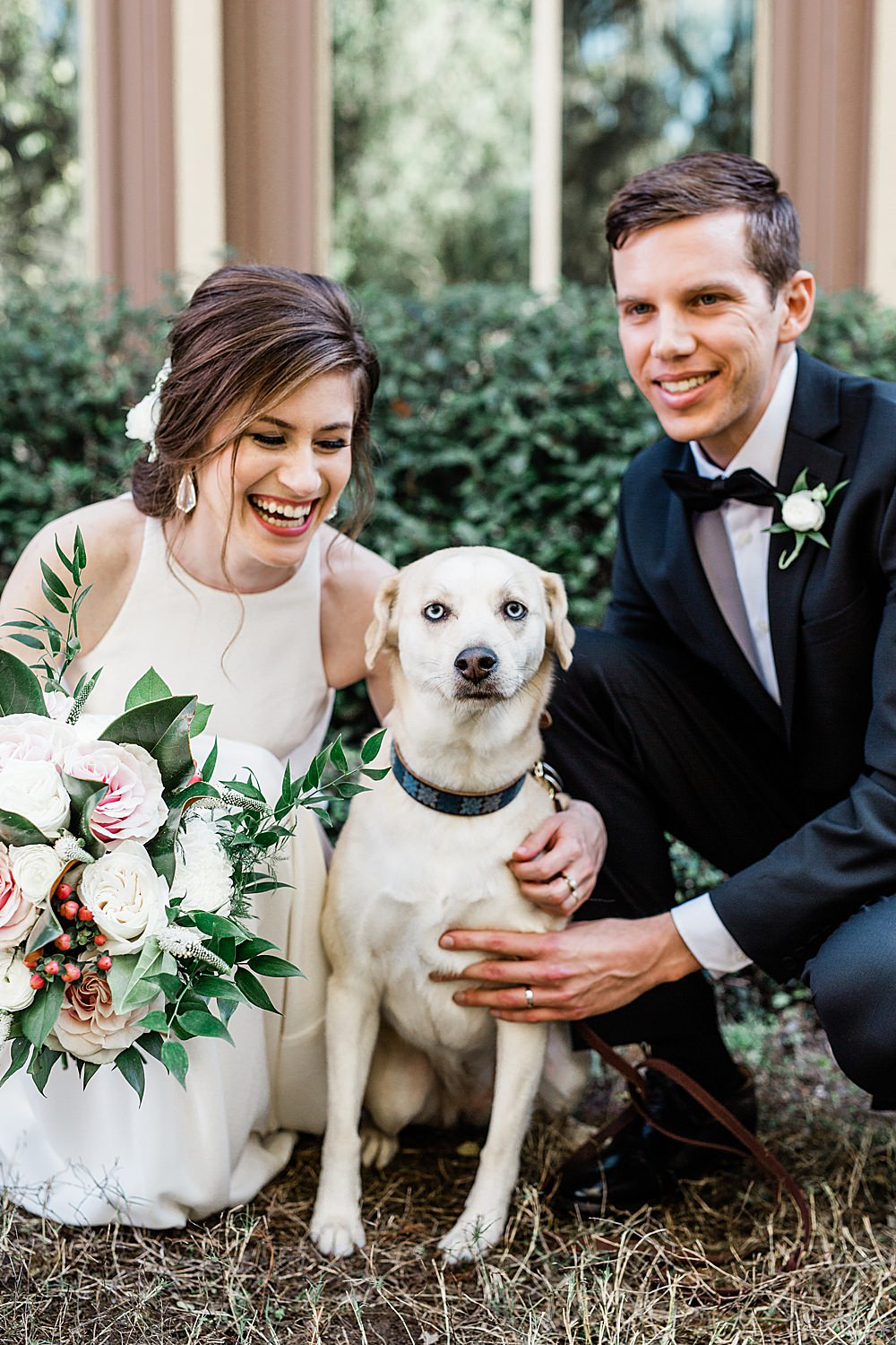 Bride and Groom smile with their puppy at their wedding