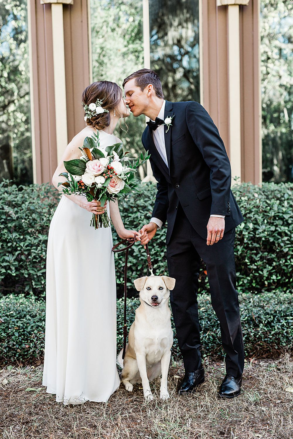 Bride and Groom kissing with their puppy