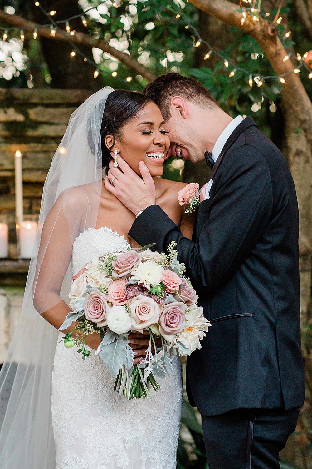 Bride and Groom laugh together under a canopy of trees