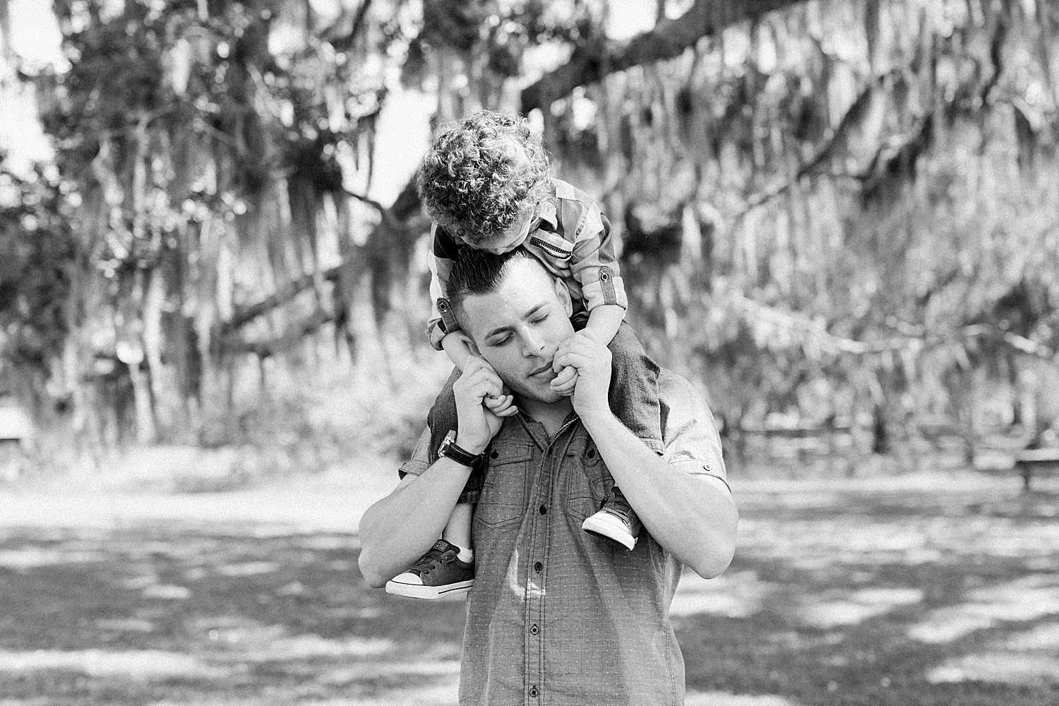 Dad and Son embrace under giant oak tree