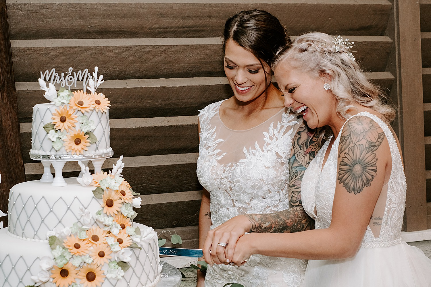 Two brides smile as they cut their wedding cake together