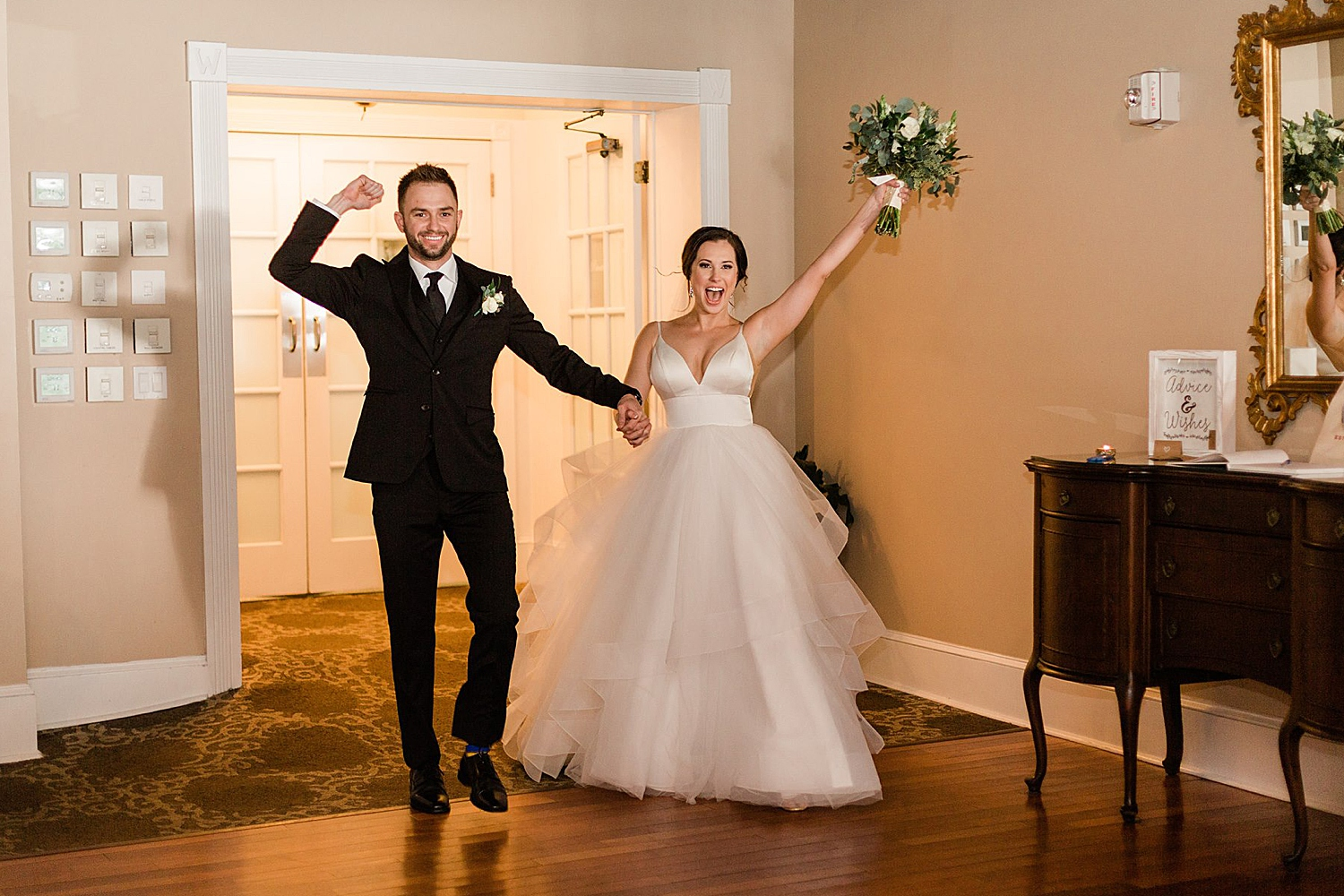 bride and groom celebrate while entering their wedding reception