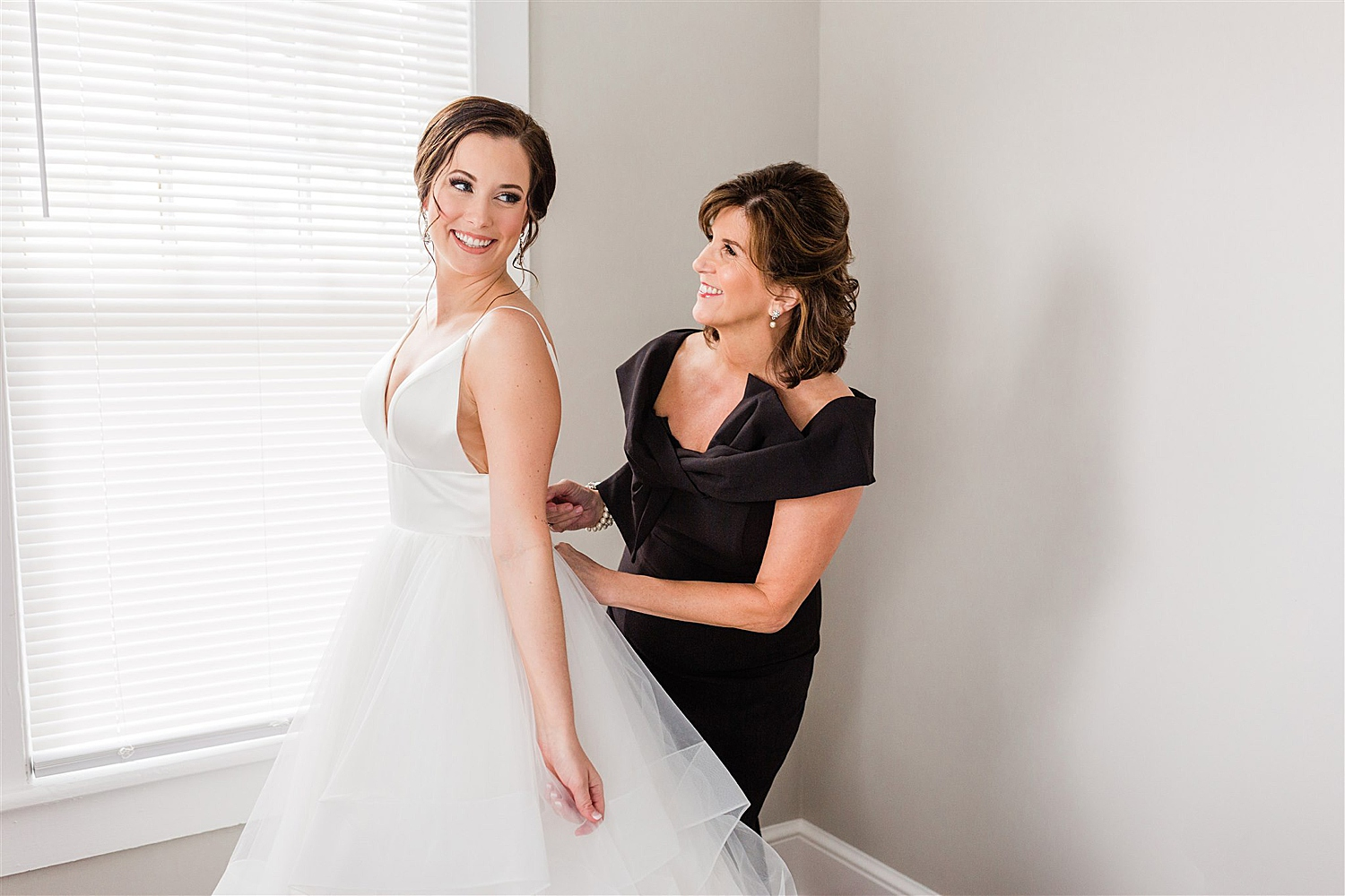 Bride's mom smiling and helping her put on her wedding dress