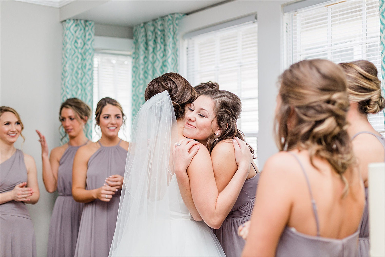 Bride hugs her crying bridesmaids after they see each other for the first time