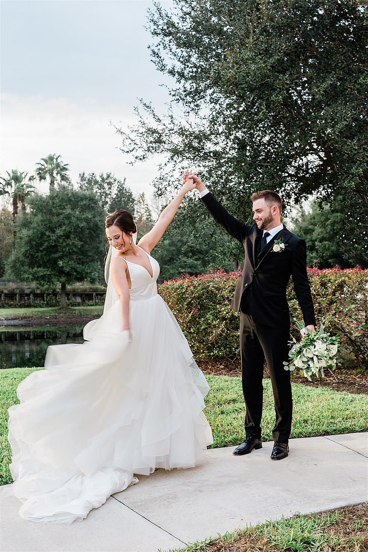 Bride twirls in her wedding dress while groom admires her
