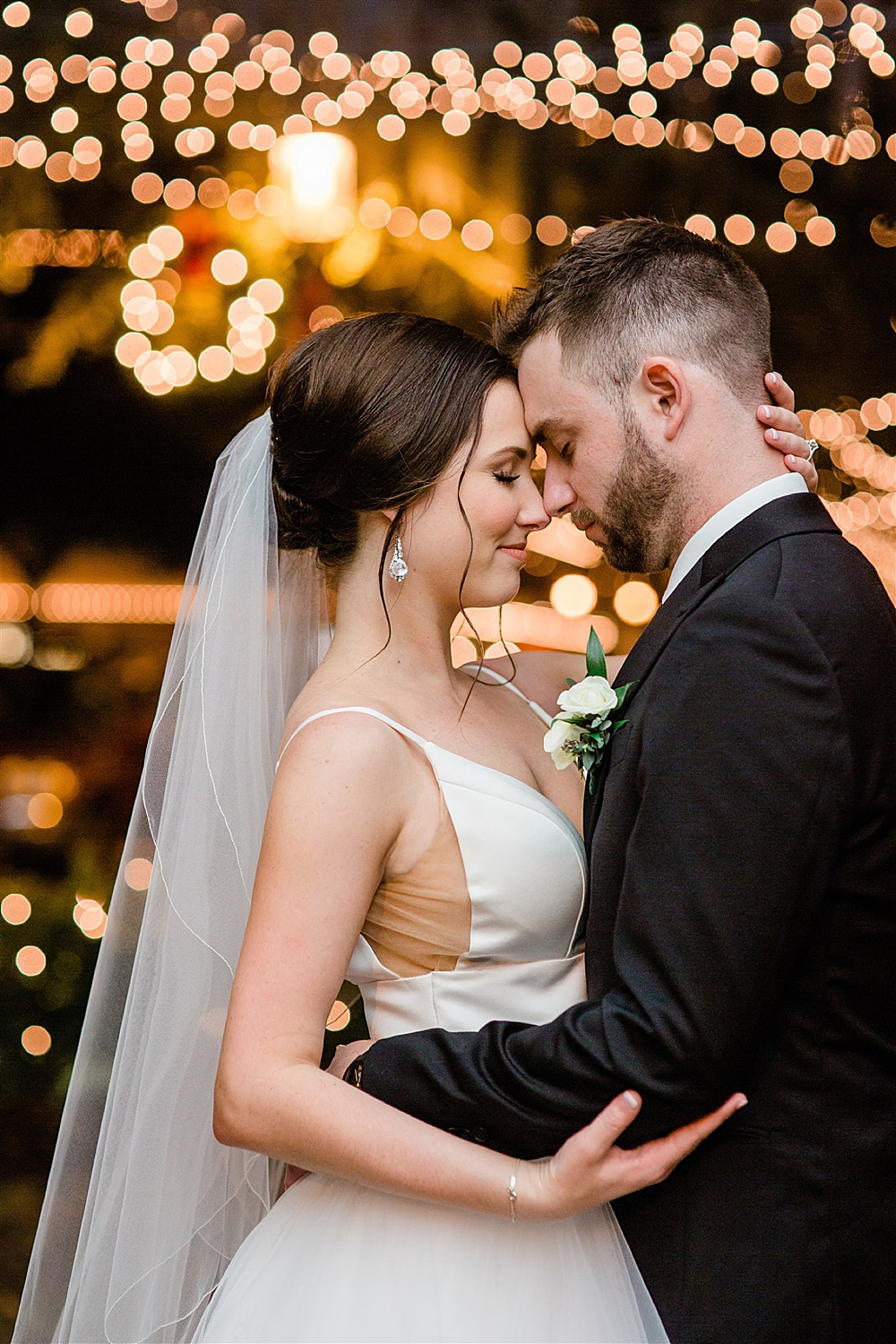 Bride and Groom share intimate embrace underneath the Night of Lights event in downtown St Augustine