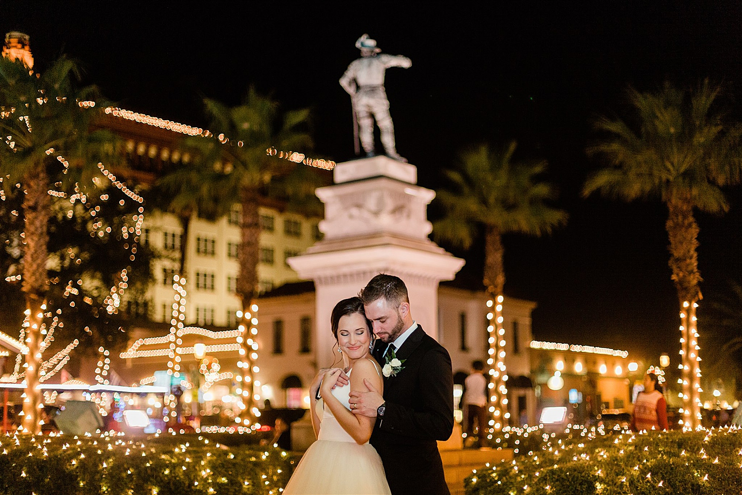 Bride and Groom smile underneath statue at the Night of Lights in st Augustine