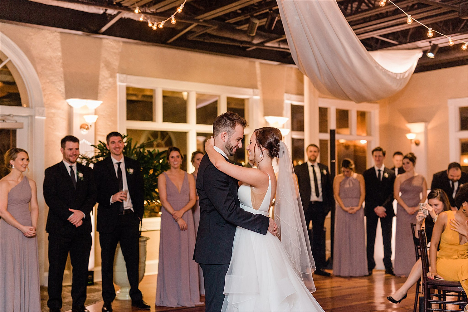 Bride and groom share their first dance at the white room while guests watch