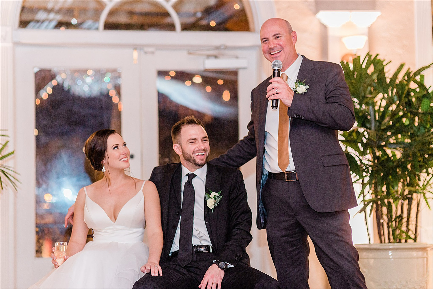 Bride and Groom laugh while bride's father gives a toast
