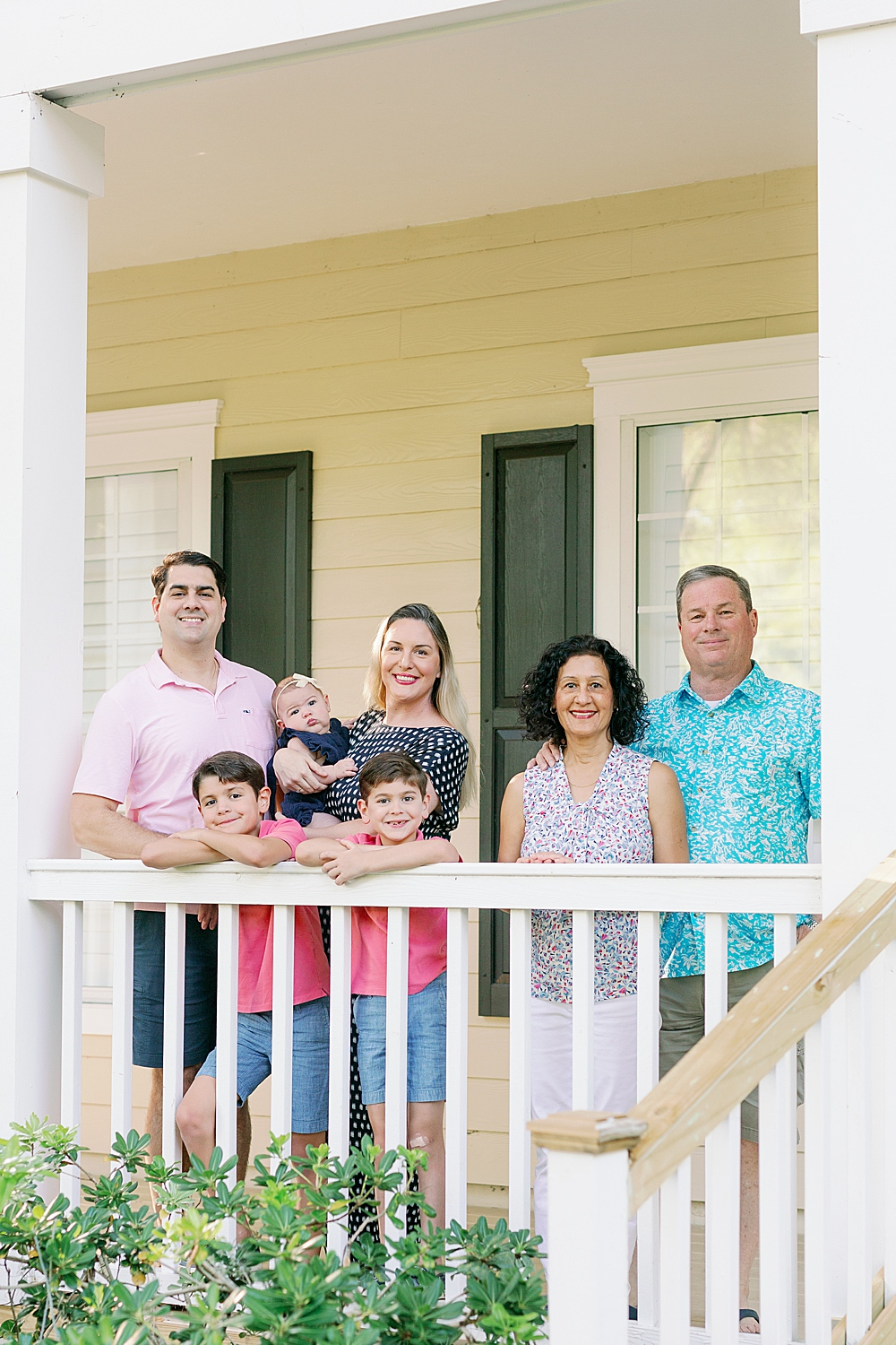 Extended family stands on their home porch and smiles at the camera