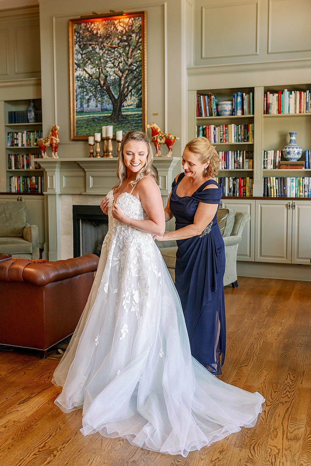 Bride being zipped up by mom on wedding day