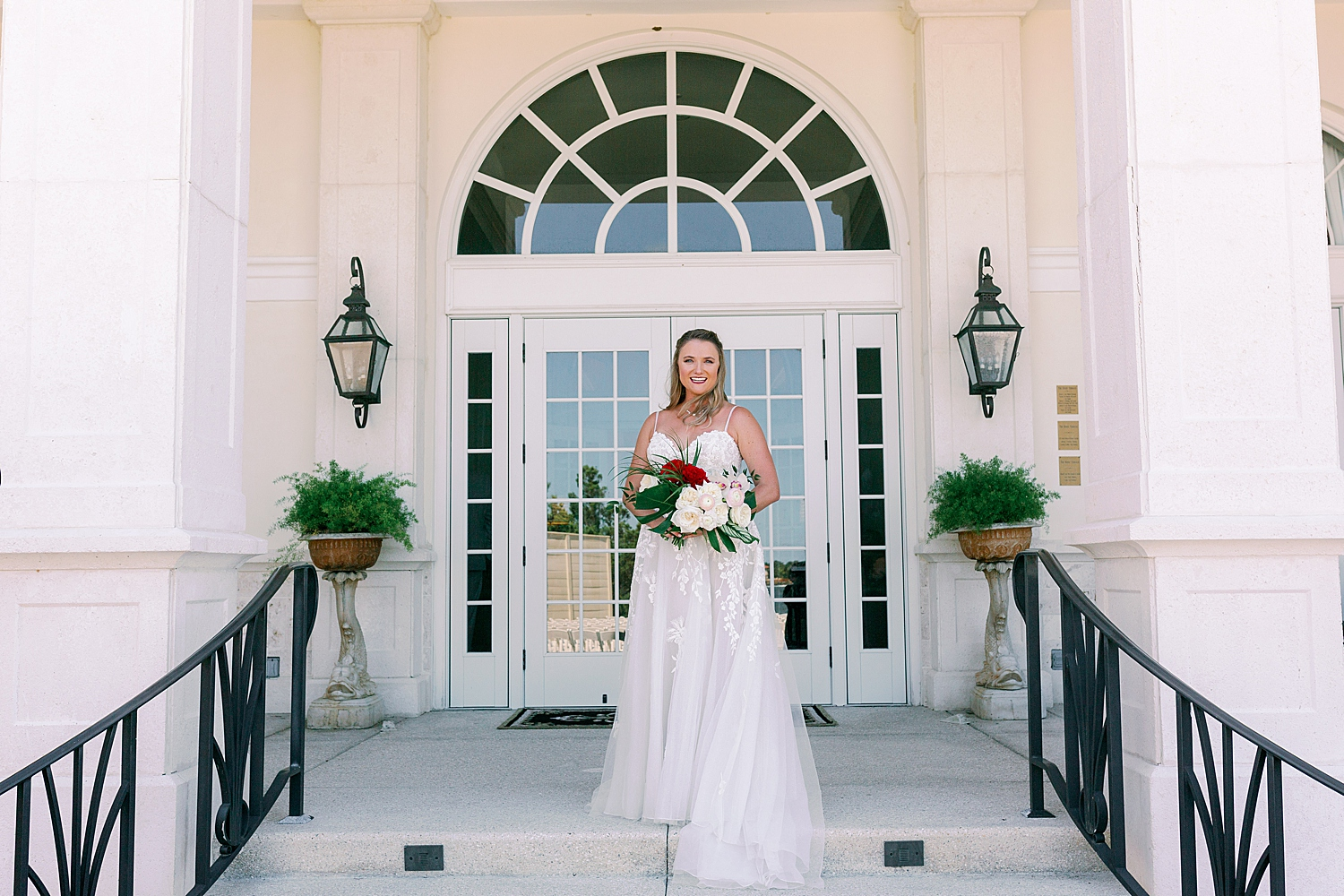 Bride smiling standing on staircase at River House