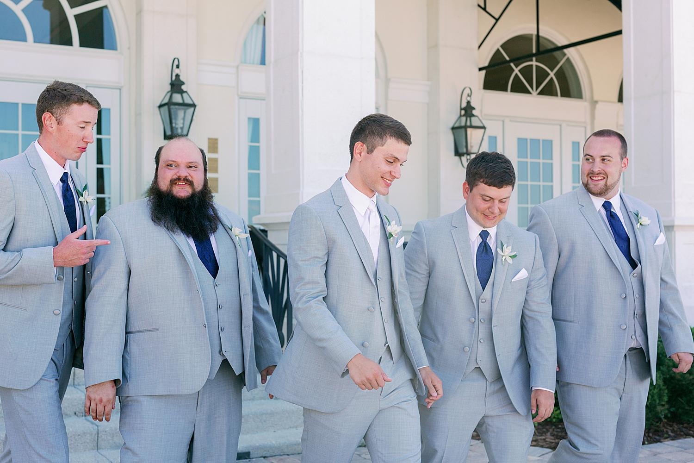 Groom walking and laughing with groomsmen