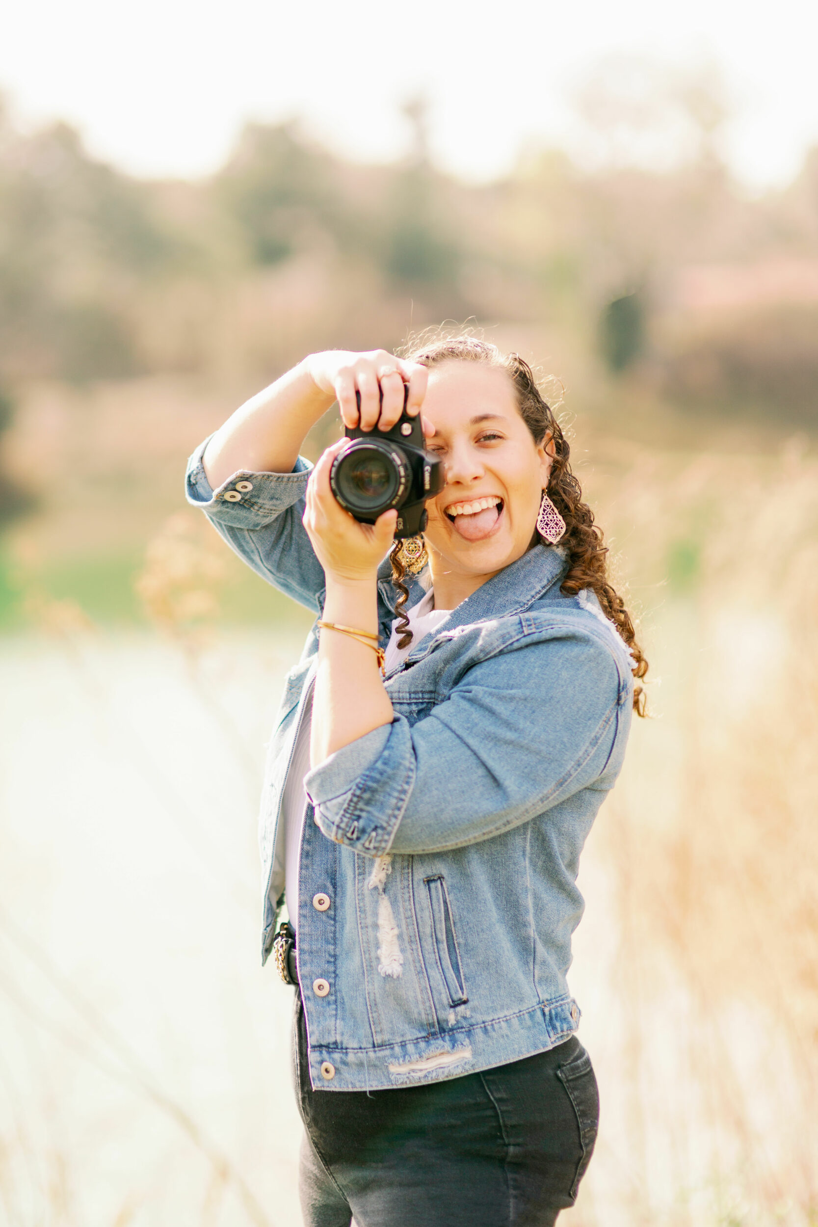 Arielle a florida wedding photographer poses with camera for lifestyle headshot