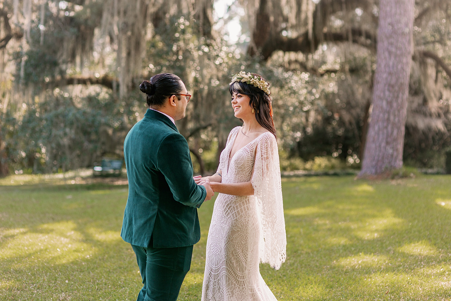 Bride and Groom smile at each other underneath mossy oak trees