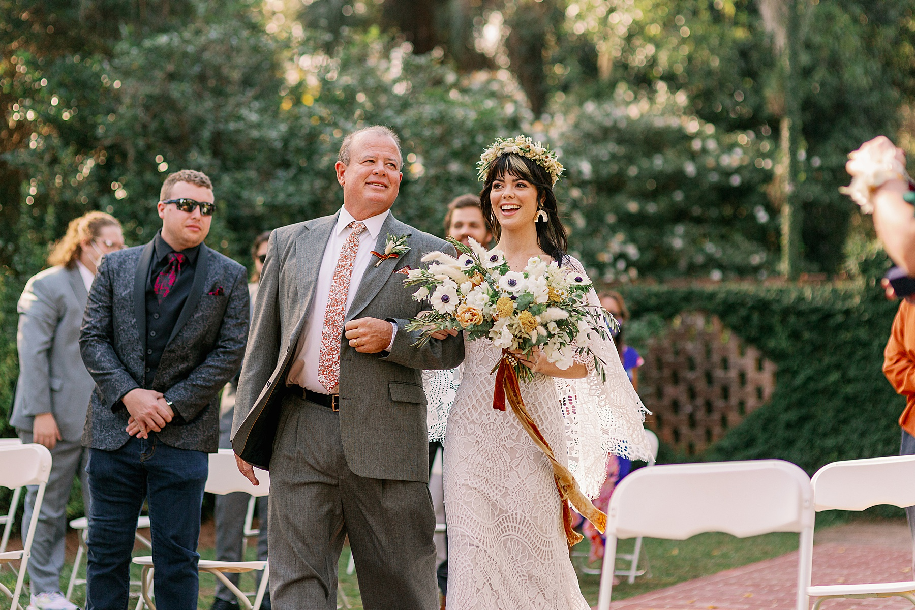 Bride walks down the aisle with her dad as she smiles at her groom