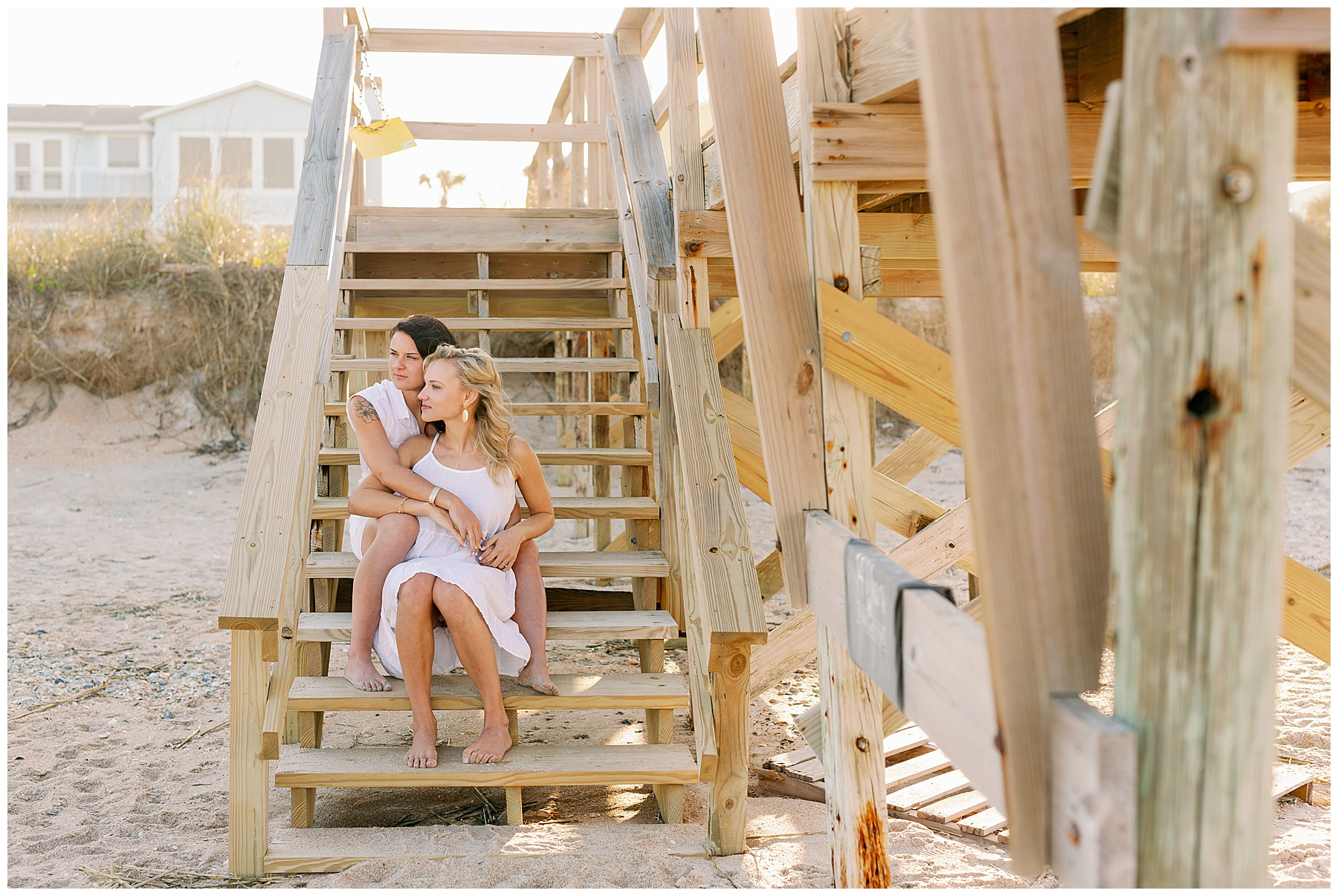 Same sex female couple embrace on the stairs at the beach bridge