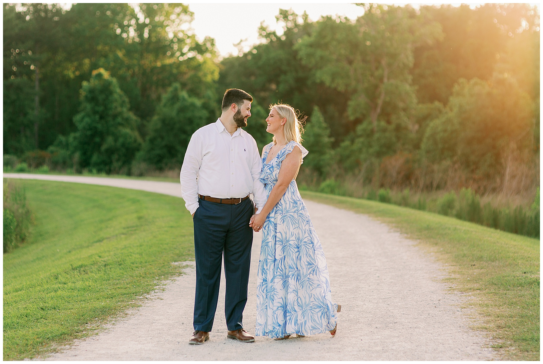 Guy and Girl look lovingly at each other holding hands on dirt path with golden glow.