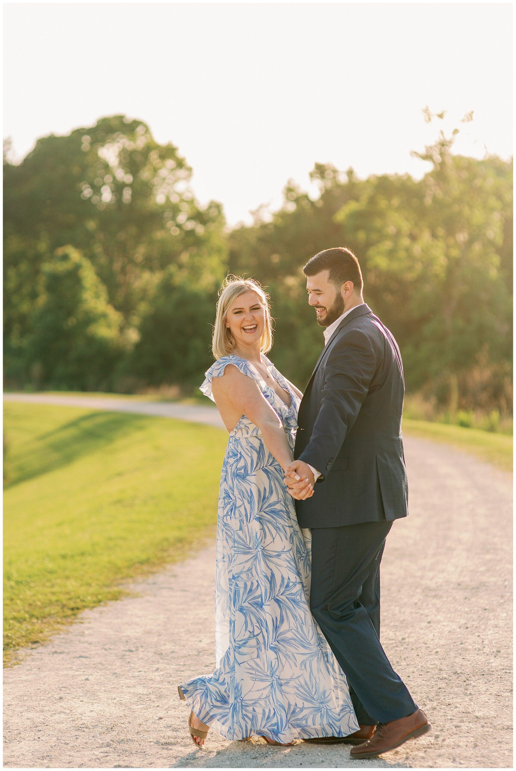 Guy and girl in blue formal wear dance on a dirt road in sun soaked photo